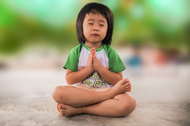 Little girl in green shirt praying