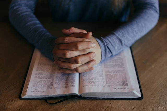 Hands in praying position, on top of a bible