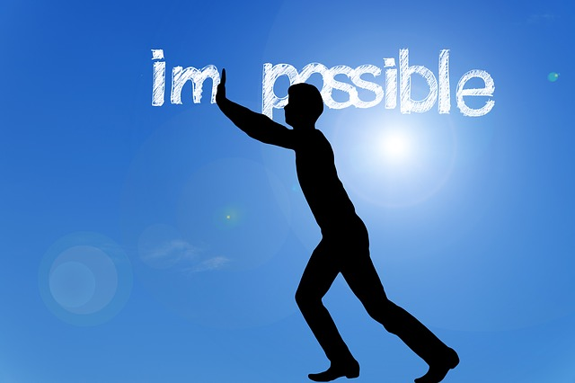 "Silhouette pushing the ""Im"" in ""Impossible"" away"