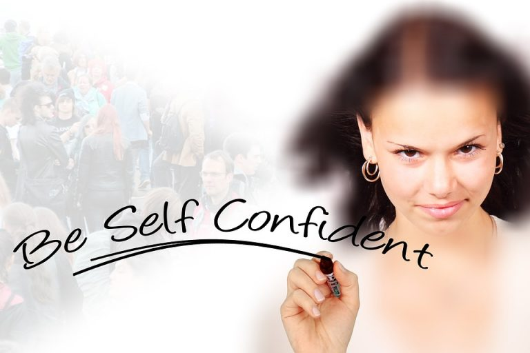 "Confident looking woman writing ""Be Self Confident"""
