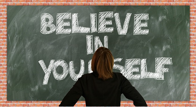 "Woman facing a board with the words ""Believe in Yourself"" on the board"