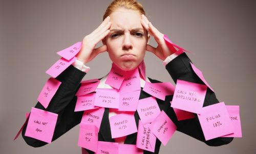 Woman holding her head, frowning, and with post its all over her body