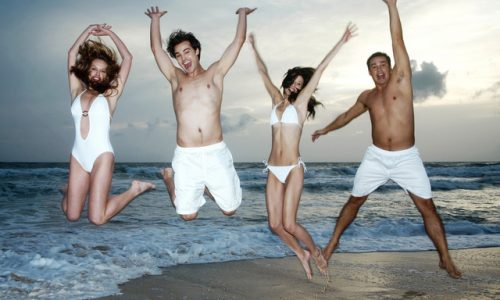 2 men 2 women jumping and looking confident and happy